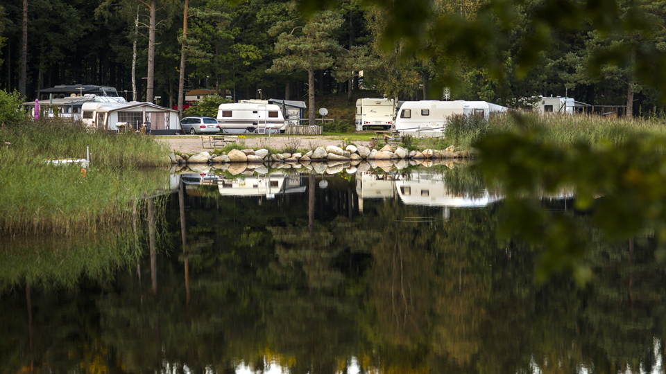 Several caravans and mobile homes are parked at Vittsjö campingsite next to the lake.