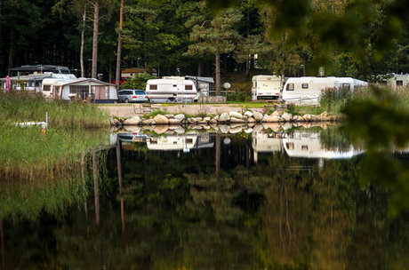 Mobile homes and caravans at a camping near water of lake Vittsjön.