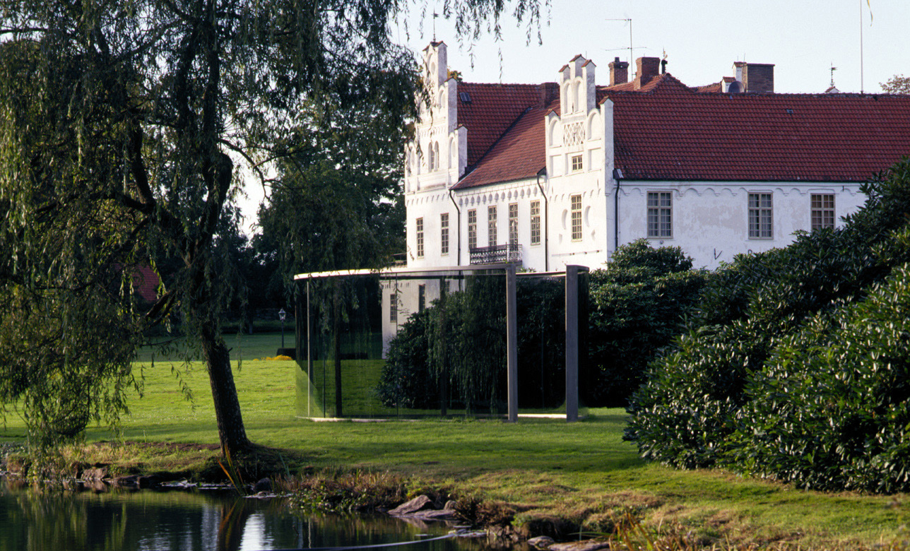 The nice white castle of Wanås lies in an art park next to a pond.