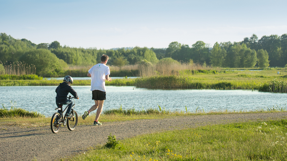 A little child is cycling beside his dad who is jogging by Magle wetlands.