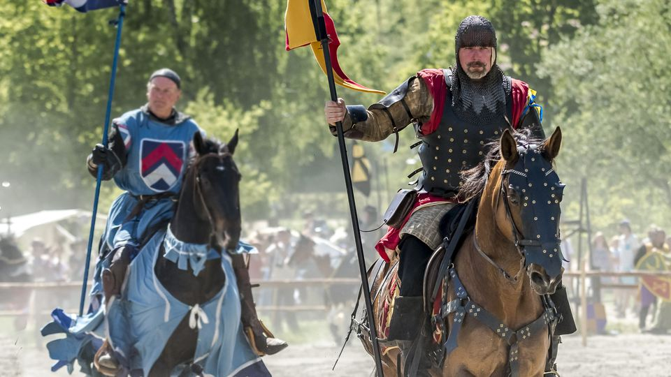 Two knights riding their horses on the tournament at Hovdala Castle.
