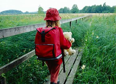 A child in red clothes with a backpack and teddy bear in her arms walks on a footpath through the reed.
